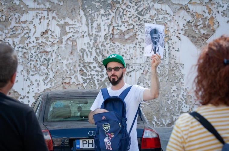 Vali Dobrin le arată turiștilor fotografia cu Brâncuși, iar în spatele său se află portretul lui Brâncuși, realizat de artistul portughez Vhils pe zidul UNARTE